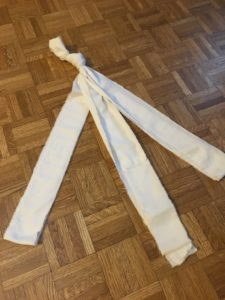 three folded bandage-strips, knotted together with an overhand knot