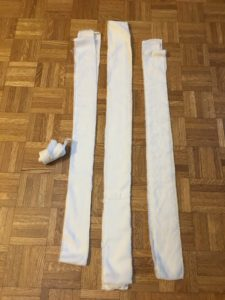 Three unrolled bandage strips, folded in fourths. One rolled bandage on the left for comparison.