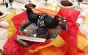 centerpiece for table with two small black and white cloth chickens sitting on a chicken soup can in the middle of a soup pot