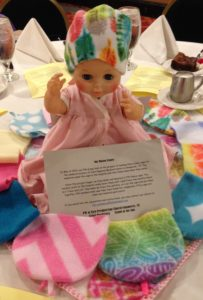 A baby doll wearing a multi-colored fleece baby cap surrounded by additional fleece baby caps in many different colors for Hunt Regional Medical Center in Greenville, TX--Grace Presbytery