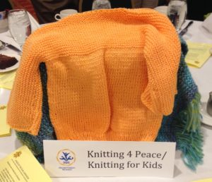 Knitted orange colored child's sweater--given to Knitting 4 Peace which distributes sweaters and other knitted items to children around the world
