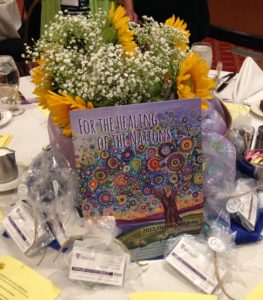 Centerpiece filled with a bouquet of baby's breath and sunflowers with the 2017 Thank Offering brochure showing a tree filled with multi-colored circles as leaves on a purple background. A Food for Thought Garden